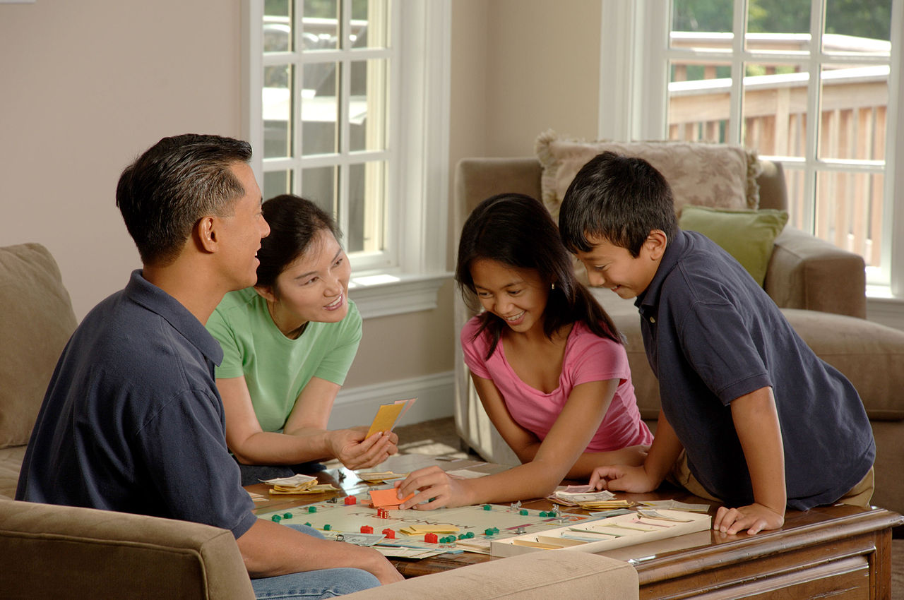 Parents and children playing board game